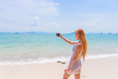 Happy attractive blonde in bikini taking a self picture on a beautiful sunny beach Royalty Free Stock Image
