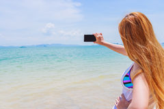 Happy attractive blonde in bikini taking a self picture on a beautiful sunny beach Royalty Free Stock Photo