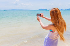 Happy attractive blonde in bikini taking a self picture on a beautiful sunny beach Royalty Free Stock Images
