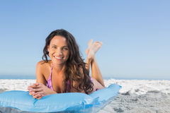 Happy attractive brunette relaxing on her lilo Royalty Free Stock Photo
