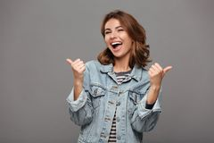 Happy attractive brunette woman in jeans jacket showing thumb up. Happy attractive brunette woman in jeans jacket showing thumbs up gesture with two hands Royalty Free Stock Photography