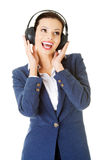 Happy attractive businesswoman listening the music through headp Royalty Free Stock Images