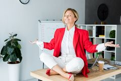 happy attractive businesswoman meditating in lotus pose on table stock photography