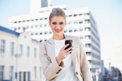 Happy attractive businesswoman sending a text message Royalty Free Stock Image