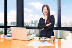 Happy attractive businesswoman standing in her office with city Royalty Free Stock Photo
