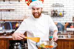 Happy attractive chef cook cooking using frying pan. On the kitchen royalty free stock photography