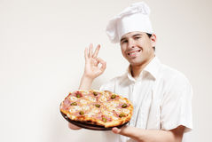 Happy attractive cook with a pizza in hands Royalty Free Stock Photo