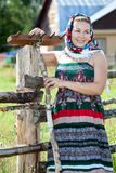 Happy attractive country girl in sundress and headscarf against house Stock Image