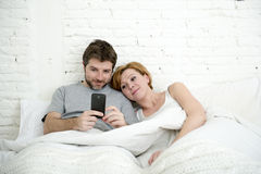 Happy attractive couple in bed using mobile phone smiling watching together internet app Royalty Free Stock Photos