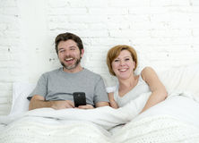 Happy attractive couple in bed using mobile phone smiling watching together internet app Stock Photography