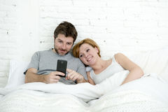 Happy attractive couple in bed using mobile phone smiling watching together internet app Stock Images