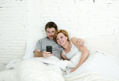 Happy attractive couple in bed using mobile phone smiling watching together internet app Stock Photos