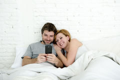 Happy attractive couple in bed using mobile phone smiling watching together internet app Royalty Free Stock Images