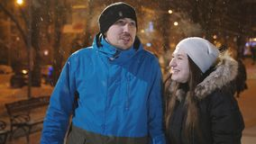 Happy attractive couple in a christmas market at night. Beautiful bokeh lights background. stock footage