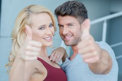Happy attractive couple giving a thumbs up Stock Images