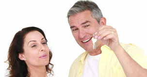 Happy attractive couple holding new house key. On white background stock video