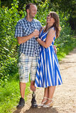 Happy attractive couple in love. Standing in a close embrace on a leafy green pathway with the men wearing a prosthetic leg following an amputation of his leg royalty free stock photos