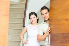 Happy attractive couple opening the door to their royalty free stock images