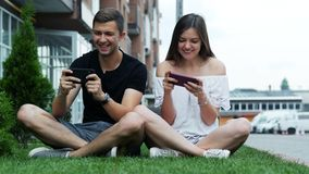 Happy and attractive couple play game on mobile phone. Caucasian man and woman spend leisure time stock video footage