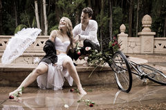 Happy attractive couple sitting at edge of fountain with vintage bicycle and roses Stock Photography