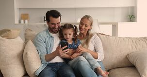 Couple and daughter relaxing on couch having fun using smartphone