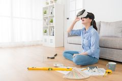 Happy attractive design new house interior plan. Happy attractive woman design new house interior plan and wearing virtual reality technology goggles looking 3D Royalty Free Stock Photography