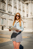Happy attractive exchange student girl visiting Madrid city reading map Royalty Free Stock Image
