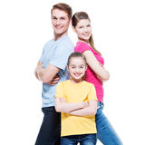 Happy attractive family with daughter. Happy attractive family with daughter standing back to back at studio - isolated on white royalty free stock images