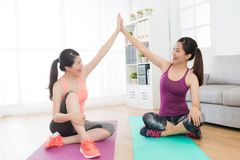 Happy female friends doing yoga fitness together. Happy attractive female friends doing yoga fitness together and giving each other hands to celebrate finishing Royalty Free Stock Image