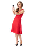 Happy attractive female in red dress takes photos. Young happy attractive female in red dress takes photos using her mobile phone, shoot over white background royalty free stock photography