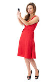 Happy attractive female in red dress takes photos. Young happy attractive female in red dress takes photos using her mobile phone, shoot over white background stock photography