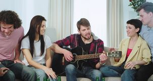 Happy and attractive friends multi ethnic enjoy the time together in a big living room they playing on a guitar singing stock video footage