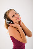 Happy attractive girl in headphones listens to mus. Happy attractive girl with headphones enjoys listening to music stock image
