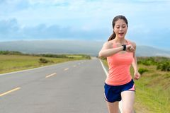 Happy attractive girl runner using smartwatch Royalty Free Stock Photography