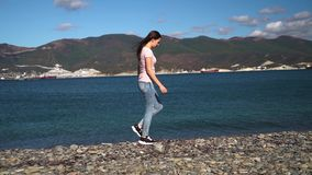 Happy attractive girl or young woman in pink shirt and blue ripped jeans walking along the sea on beach slow motion stock video