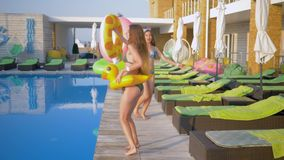 Happy attractive girlfriends into bathing suit with Inflatable rings walk near pool during summer holiday at resort