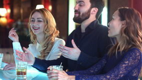 Happy and attractive group of friends chatting and laughing together in a bar stock video