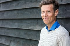 Happy Attractive Handsome Middle Aged Man. Portrait shot of an attractive, handsome, successful and happy middle aged man male outside wearing a sweater Royalty Free Stock Photo