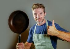 Happy attractive home cook man with cooking pan smiling satisfied and proud giving thumb up domestic chef and house husband lifest. Young happy and attractive stock image