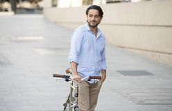 Happy attractive latin man in casual trendy clothes smiling cheerful riding on vintage cool retro bicycle Stock Image