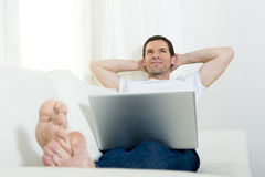 Happy attractive man freelance working with computer laptop laying on couch at home relaxed Royalty Free Stock Photos