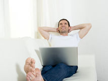 Happy attractive man freelance working daydreaming with computer laptop layi Royalty Free Stock Image