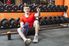 Happy attractive man resting after a workout and shows his thumb up at the gym. stock photo