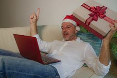 happy and attractive man in Santa Klaus hat using credit card and laptop computer buying online Christmas present holding gift box stock images