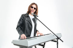 Happy attractive man singing in microphone and playing on synthesizer. Happy attractive young man in sunglasses with long hair singing in microphone and playing Royalty Free Stock Photography