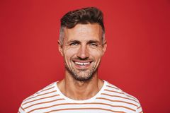 Happy attractive man with stubble in striped t-shirt smiling on. Camera, isolated over red backgroun stock photography