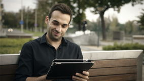 Happy attractive man using tablet PC outside on a park bench. Happy businessman using digital tablet at park stock video footage
