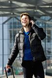 Happy attractive man walking and talking on mobile phone Stock Photo