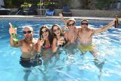Happy attractive men and women in bikini having bath at hotel resort swimming pool drinking beer Stock Photo