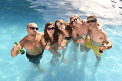 Happy attractive men and women in bikini having bath at hotel resort swimming pool drinking beer Stock Photos